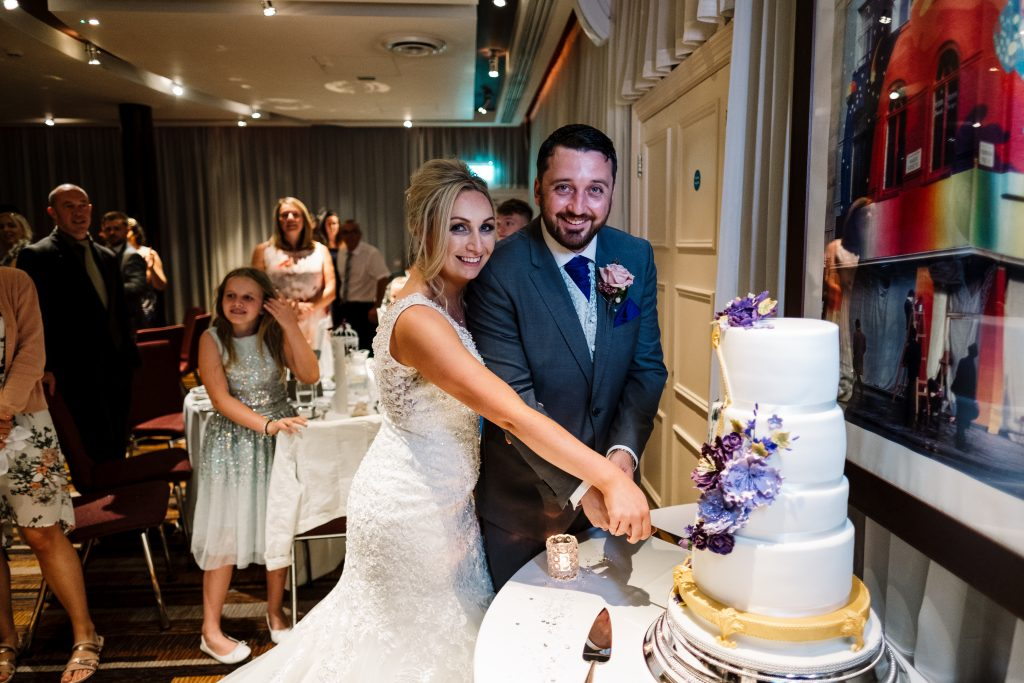 bride and groom smile as they pose for a cake cut photo in the Zygmant suite