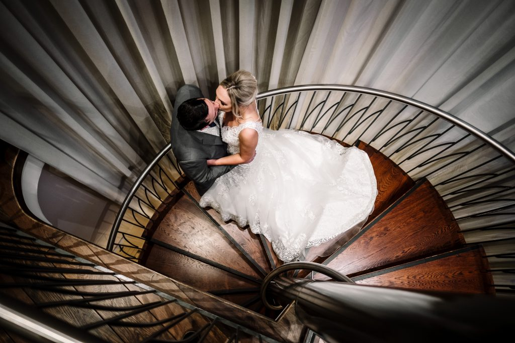 bride and groom kiss on the spiral staircase leading to 'The Two of us' suite