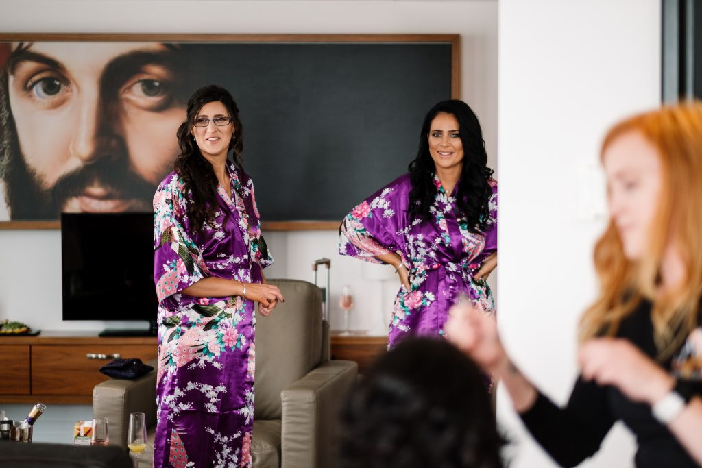 bridesmaids wearing bright purple wraps during bridal preparations