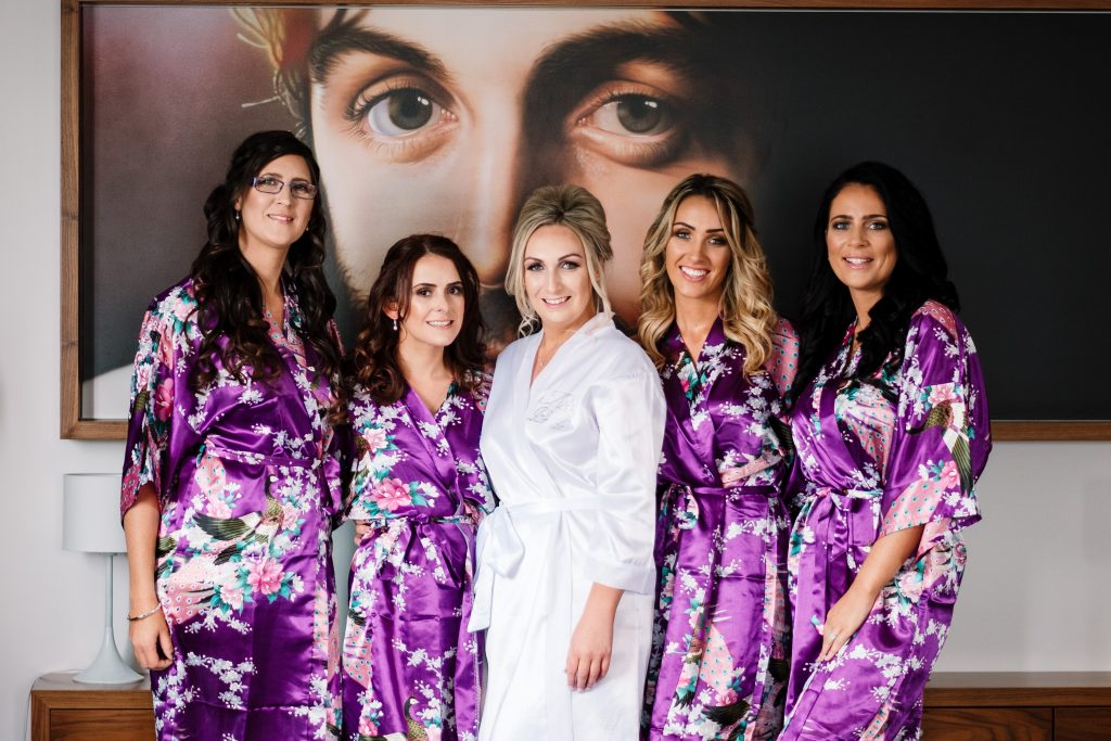 bride group portrait with bridesmaids wearing purple gowns