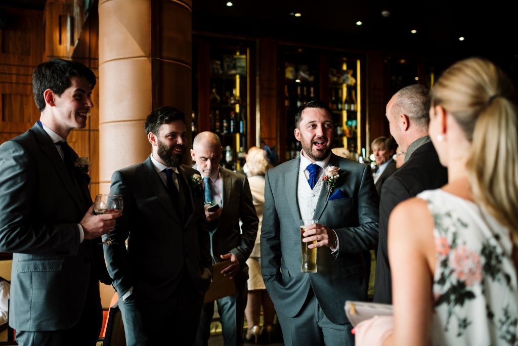 groom laughing with wedding guests before the wedding ceremony
